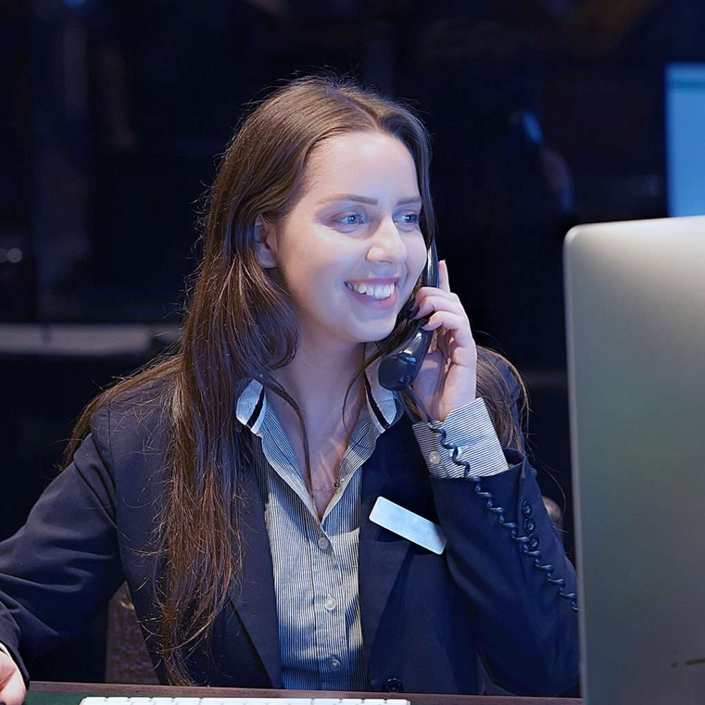 Kvinde ved computerskærm taler i telefon