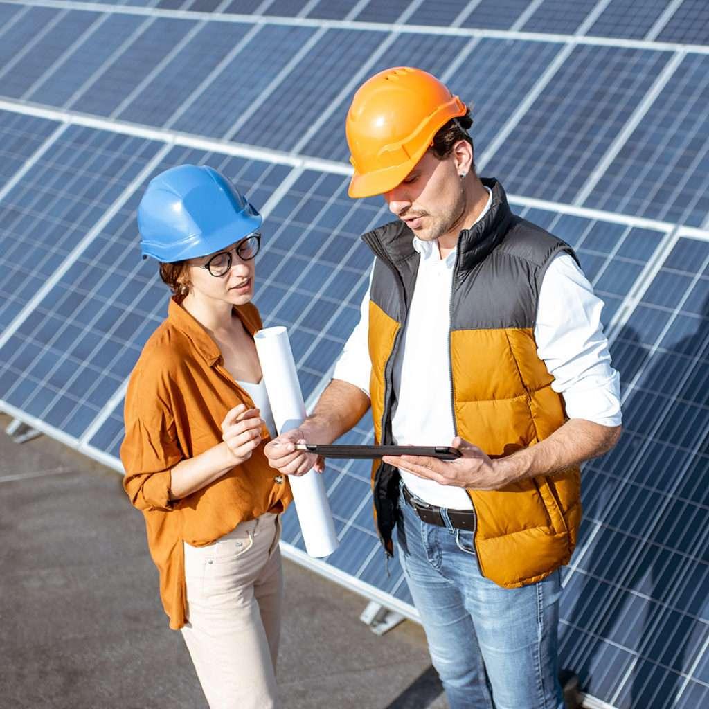 Mand og kvinde med beskyttelseshjelm ved solpaneler