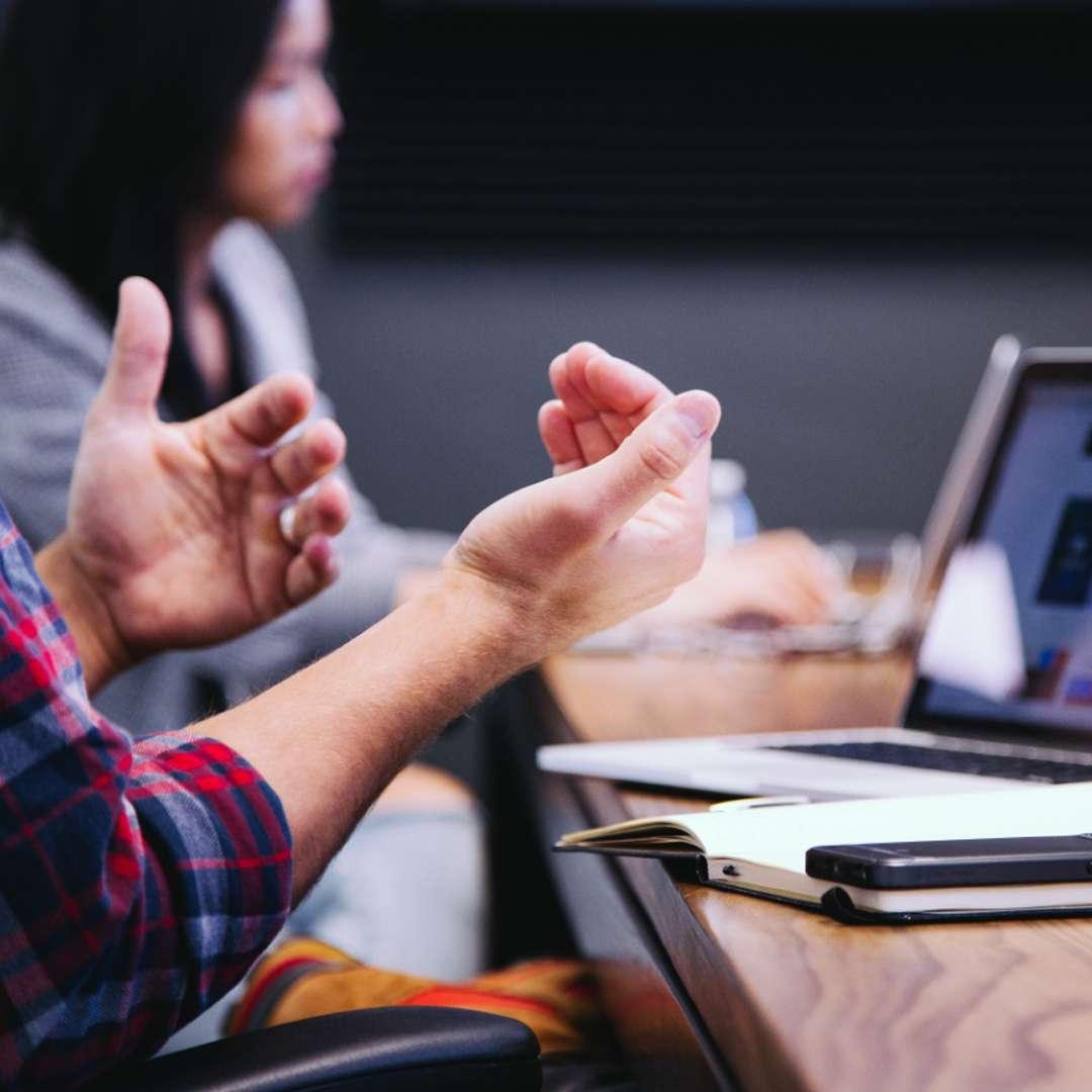 Close-up af en mands hænder menes han taler ved et møde