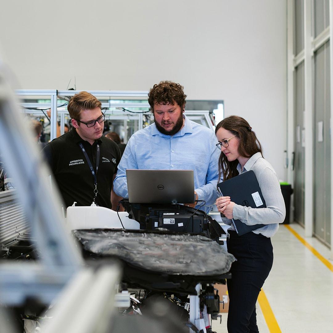 To mænd og en kvinde ser på en computerskærm i en fabrik